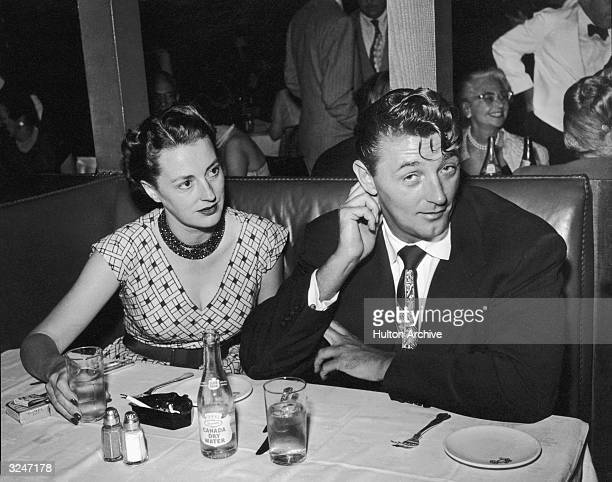 American actor Robert Mitchum sits in a restaurant booth with his wife Dorothy