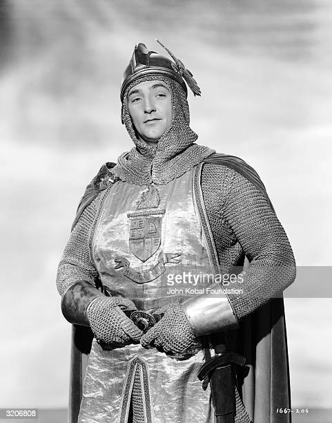 American actor Robert Mitchum wearing chain mail and a helmet.