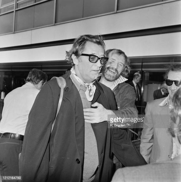 American actor Robert Mitchum wearing sunglasses as Irish actor Richard Harris laughs and pats Mitchum on the chest at Heathrow Airport in London...