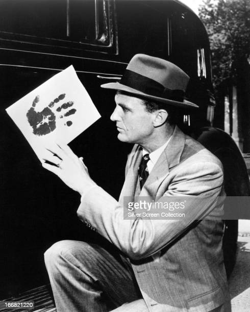 American actor Robert Stack as Eliot Ness holding a handprint in the TV crime series 'The Untouchables' circa 1960
