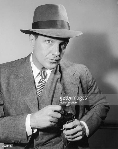 American actor Robert Stack in costume as Eliot Ness holds a gun tucked in a shoulder holster in a promotional portrait for the television series...