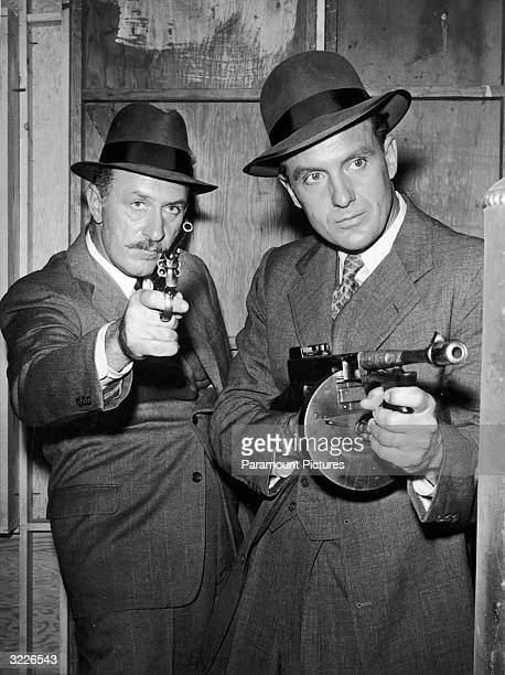 American actor Robert Stack playing Eliot Ness and American actor Keenan Wynn playing Ness' cohort Joe Fuselli aim their guns while raiding an Al...