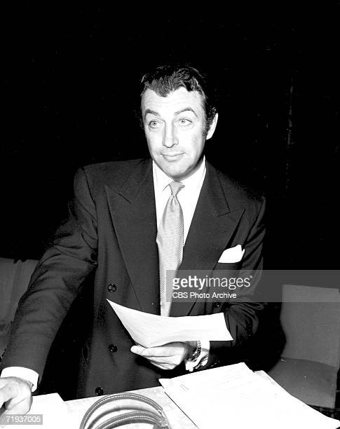 American actor Robert Taylor holds the script as he prepares for the bordcast of the story 'Westward the Women' on the CBS radio anthology series Lux...