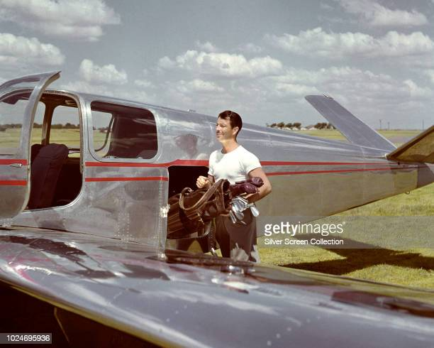 American actor Robert Taylor loads his golf clubs onto a private aircraft circa 1955