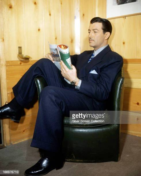 American actor Robert Taylor sitting in an armchair and reading a magazine circa 1940