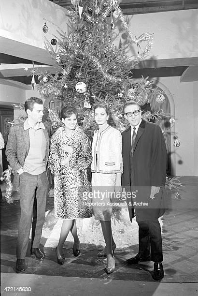 'American actor Robert Wagner British actor Peter Sellers Italian actress Claudia Cardinale and French actress Capucine posing next to a Christmas...