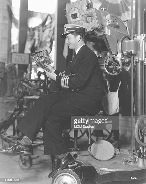 American actor Robert Young on the set of 'Tugboat Annie' directed by Mervyn LeRoy 1933 Young is looking at stills of his costars Marie Dressler and...
