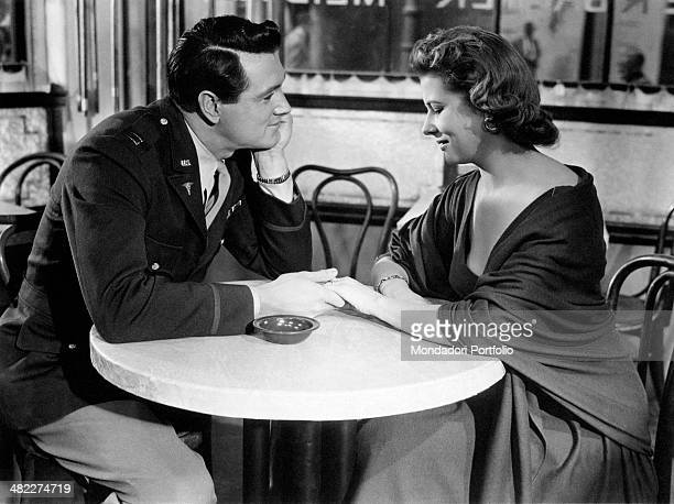 American actor Rock Hudson and German actress Cornell Borchers sitting hand in hand at a table in the film Never Say Goodbye 1956