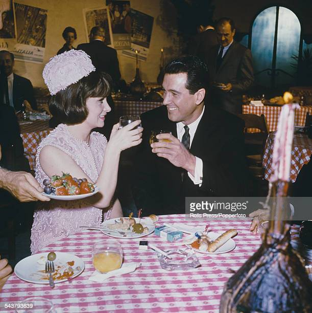American actor Rock Hudson and Italian actress Gina Lollobrigida who appeared together in the film 'Come Together' are pictured enjoying a restaurant...