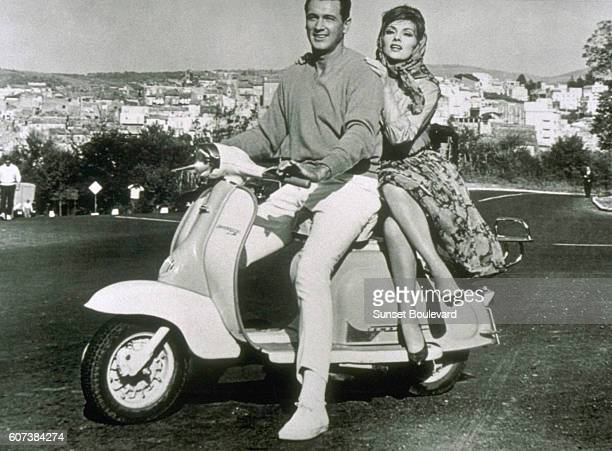 American actor Rock Hudson as Robert L Talbot and Italian actress Gina Lollobrigida as Lisa Helena Fellini riding a Vespa motorscooter in Italy in...