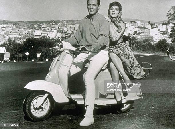 American actor Rock Hudson as Robert L. Talbot, and Italian actress Gina Lollobrigida as Lisa Helena Fellini, riding a Vespa motorscooter in Italy in...