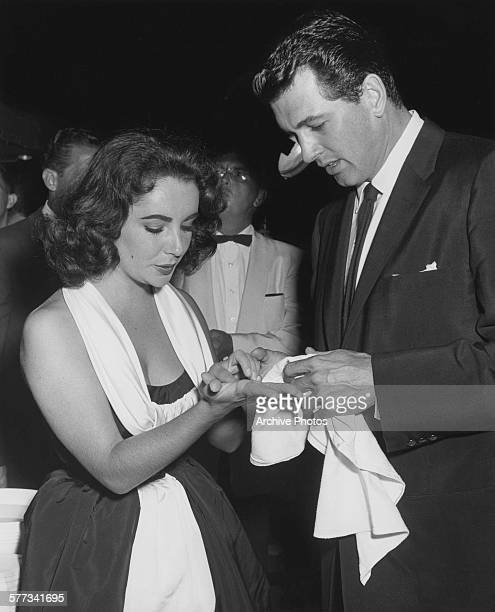 American actor Rock Hudson dries the hands of actress Elizabeth Taylor after a handprint and footprint ceremony at Grauman's Chinese Theatre in Los...