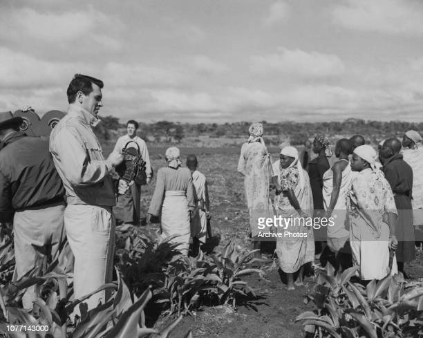 American actor Rock Hudson takes photographs of female Kikuyu farmer workers on the Burguret farm at Nanyuki Kenya during the location filming of the...