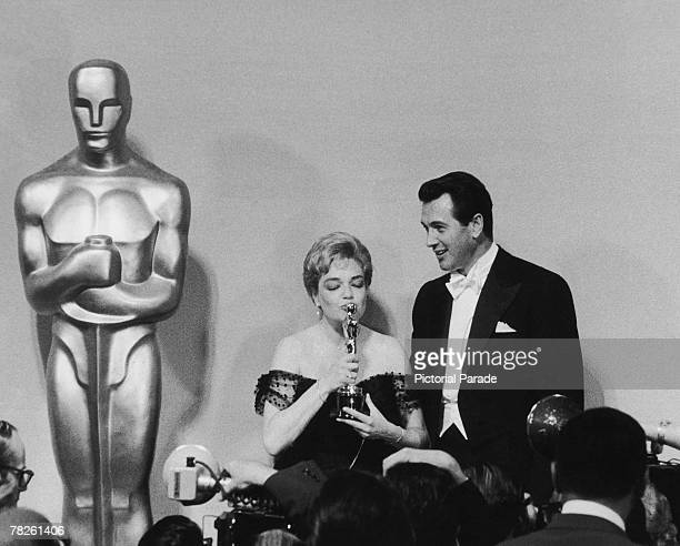 American actor Rock Hudson with French actress Simone Signoret at the Academy Awards ceremony held at the RKO Pantages Theatre Los Angeles California...