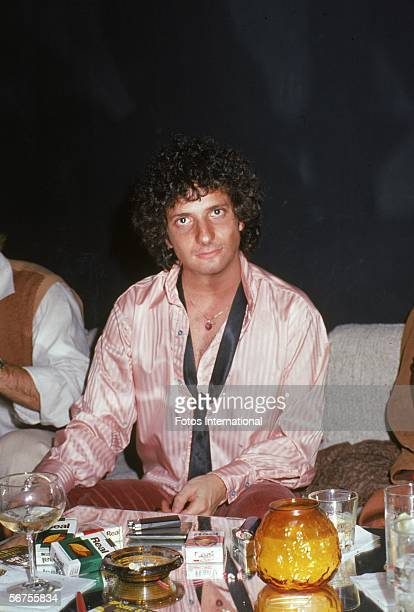 American actor Ron Palillo wears a silk shirt as he sits at a table crowded with cigarette packets and smoking accutrements at a nightclub late 1970s