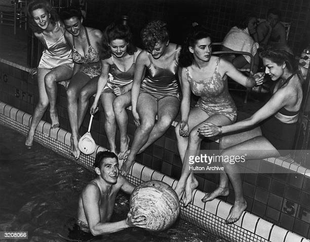 American actor Ronald Reagan grasps a beach ball in a swimming pool as six female actors wearing swimsuits sit on the edge of the pool on board the...