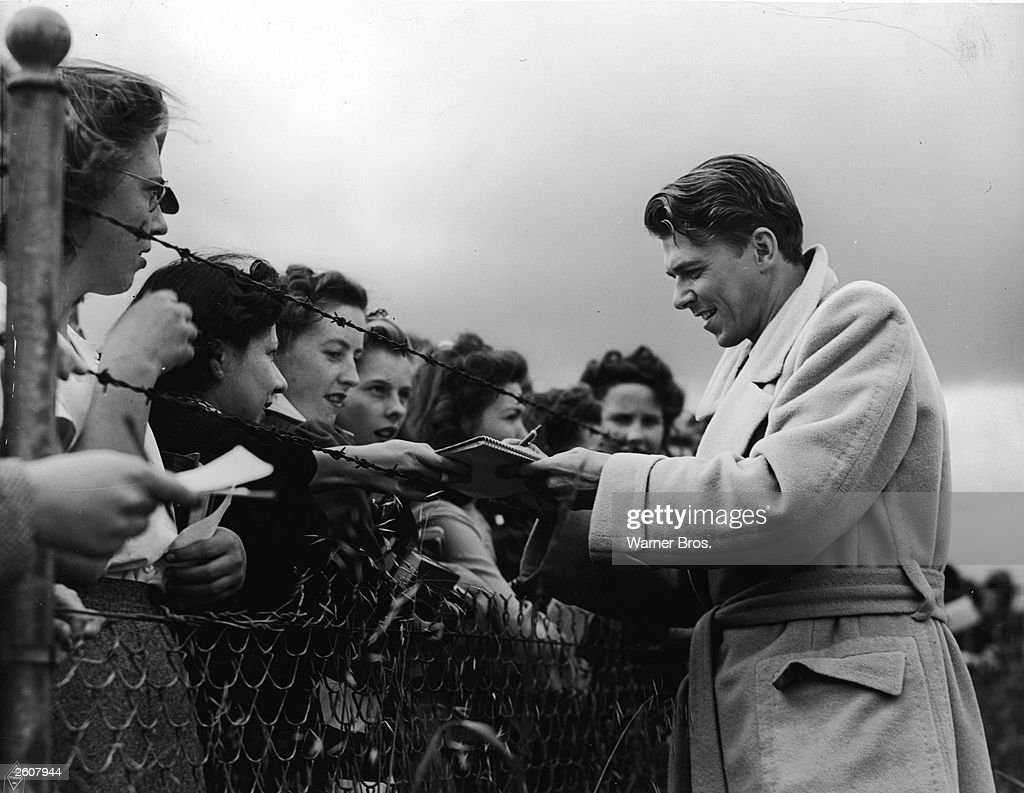 American actor Ronald Reagan signs autographs for female fans through a barbed wire fence, 1940s.