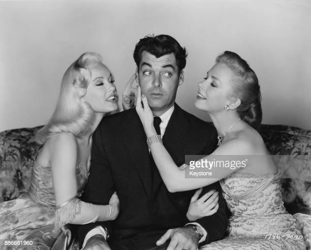 American actor Rory Calhoun with actresses Piper Laurie and Mamie Van Doren in a publicity still for the 1955 comedy romance 'Ain't Misbehavin''