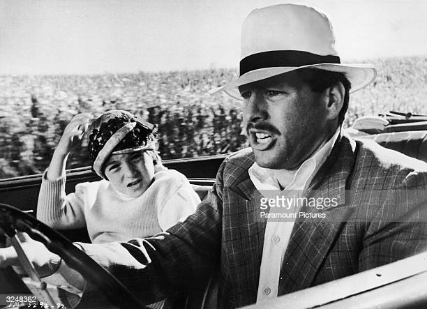 American actor Ryan O'Neal drives a car while his daughter American actor Tatum O'Neal holds on to her hat in the passenger's seat in a still from...