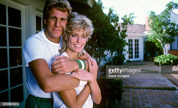 American actor Ryan O'Neal with his arm around his wife American actress Farrah Fawcett circa 1980