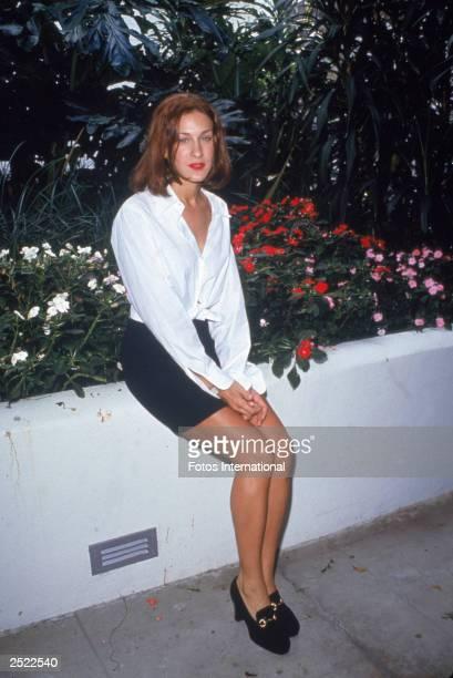 American actor Sarah Jessica Parker sits outdoors beside a flower garden circa 1990