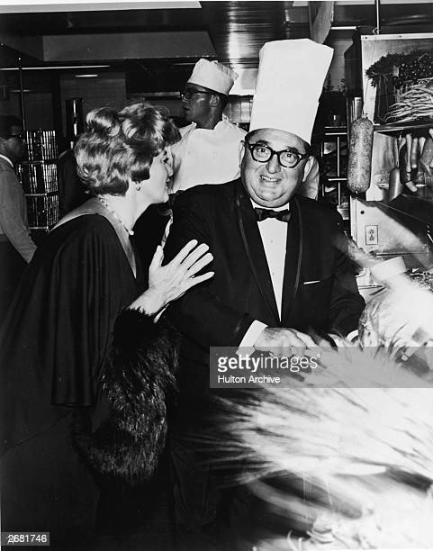 American actor Shelley Winters talks to film producer Joseph E Levine in a kitchen during the gala premiere for the film 'A House Is Not A Home'...