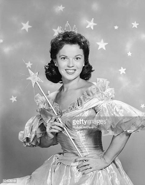 American actor Shirley Temple wears a fairy godmother costume which includes a magic wand and a tiara in a promotional portrait for her television...