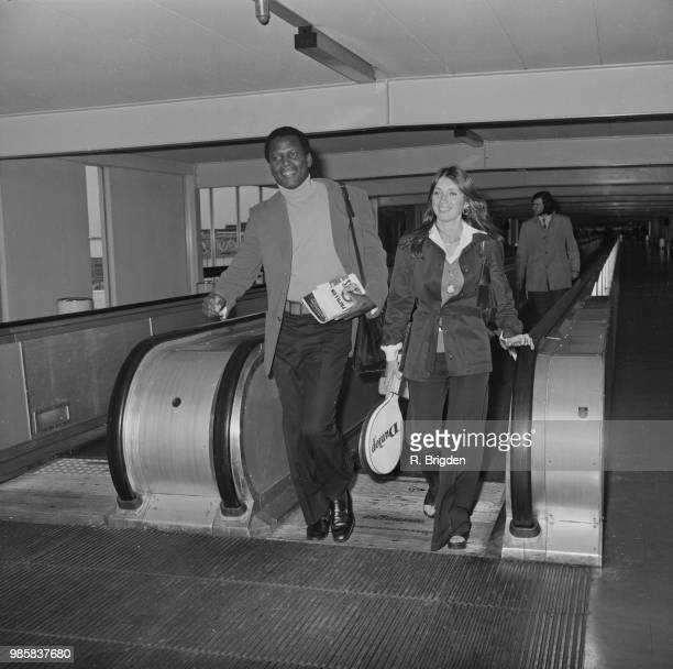 American actor Sidney Poitier and Canadian actress Joanna Shimkus pictured on a moving walkway at Heathrow airport in London on 11th September 1972