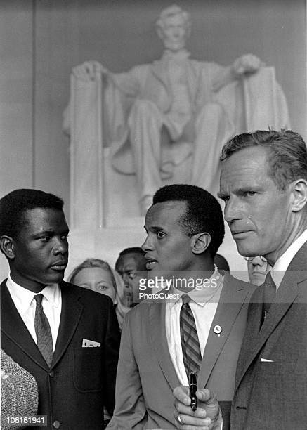 American actor Sidney Poitier listens to singer Harry Belafonte as actor Charleton Heston stands with them in the Lincoln Memorial during the March...
