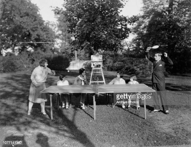 American actor singer and comedian Eddie Cantor playing table tennis with his wife Ida and their family on the lawn of their new mansion in Long...