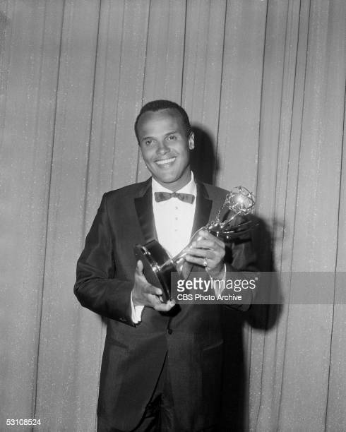American actor, singer, and composer Harry Belafonte poses in front of a glittery curtain with the Emmy statue that he had just won for his CBS...