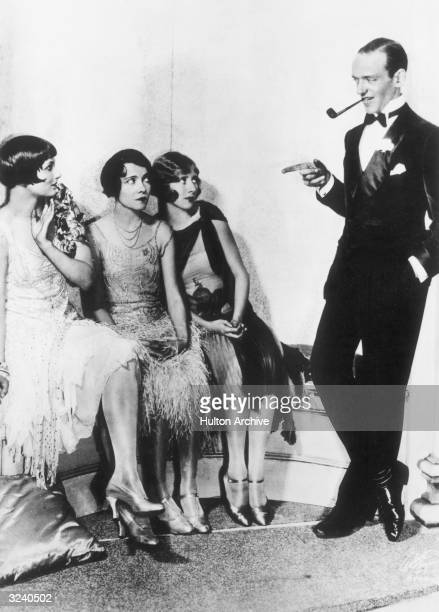 American actor singer and dancer Fred Astaire leans against a wall with a pipe in his mouth pointing as American actors Betty Compton Adele Astaire...