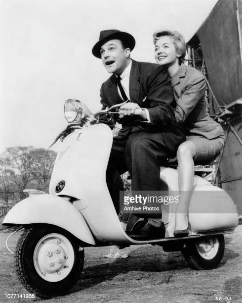 American actor singer and dancer Gene Kelly takes French actress Barbara Laage his costar in the MGM film 'The Happy Road' for a spin on a Vespa...