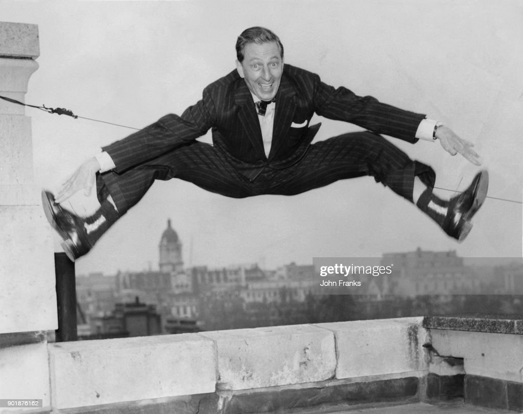 American actor, singer and dancer Ray Bolger (1904 - 1987) dances on the roof of Television House in London, after a press reception, 5th March 1958. He is about to appear on the television programme 'Sunday Night at the London Palladium'.