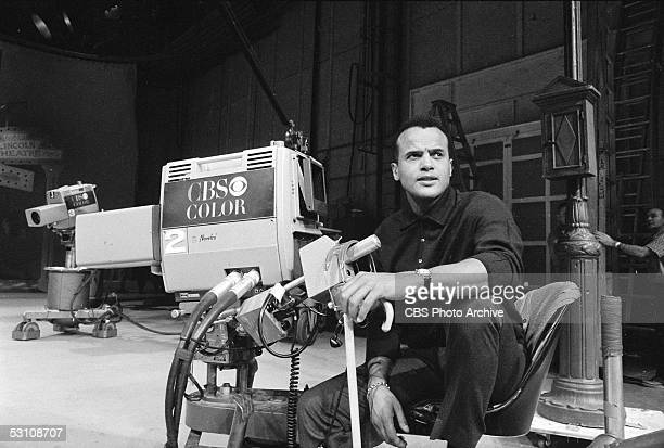 American actor, singer, and producer Harry Belafonte sits in a chair behind a CBS television camera on the set of his television special 'The...