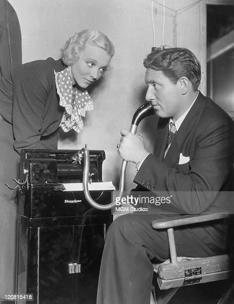 American actor Spencer Tracy plays a newspaper reporter using a dictaphone as actress Virginia Bruce looks on in a publicity still for 'The Murder...