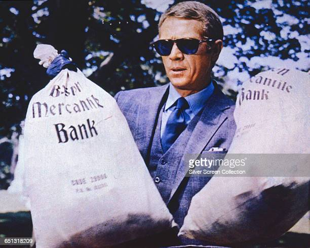 American actor Steve McQueen as the titular thief holding two sacks from the Boston Mercantile Bank in a scene from the heist film 'The Thomas Crown...