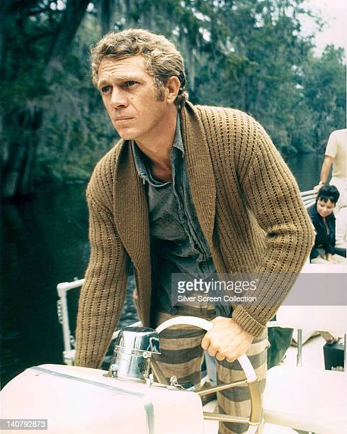 Steve McQueen US actor wearing a brown cardigan as he stands at the wheel of a boat circa 1965