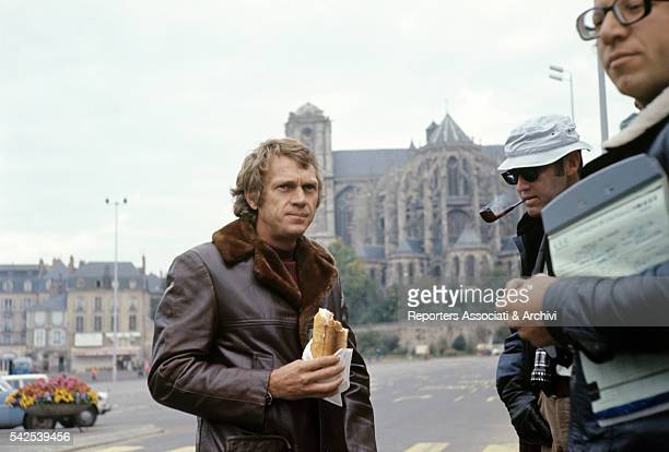 American actor Steve McQueen eating a sandwitch on the set of Le Mans 1971