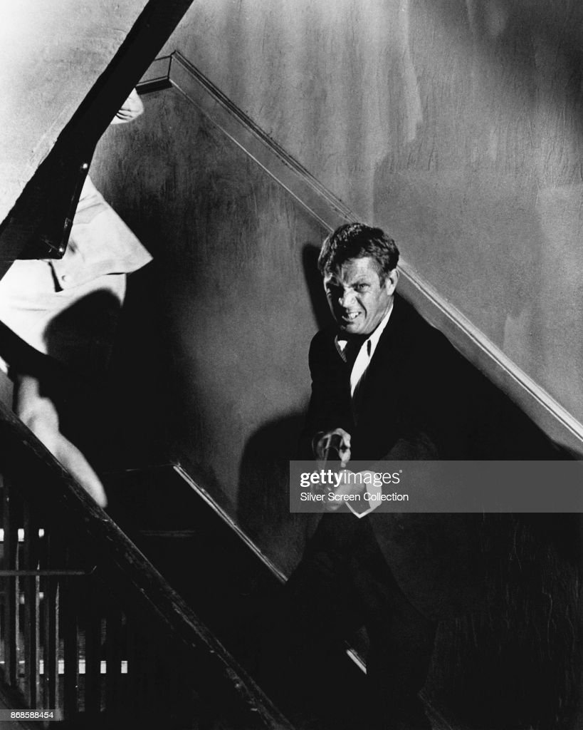 American actor Steve McQueen (1930 - 1980) (as Doc McCoy) grimaces as he aims a shotgun from a staircase in a scene from the film 'The Getaway' (directed by Sam Peckinpah), 1972.