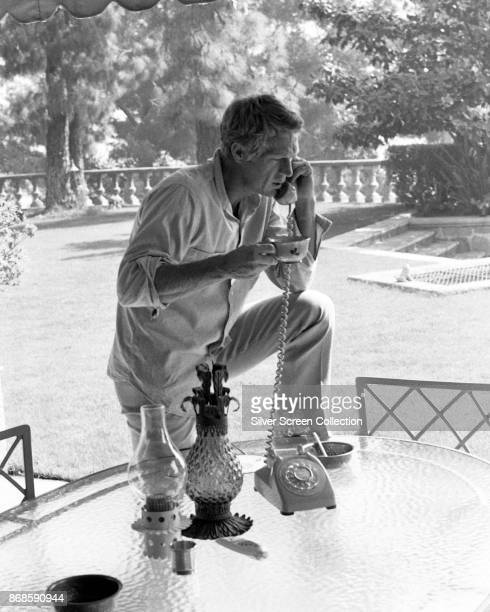 American actor Steve McQueen holds a cup as he talks on the telephone at an outdoor table in his garden, Brentwood, Los Angeles, California, 1960s.