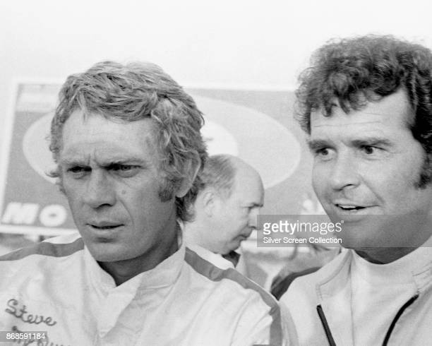 American actor Steve McQueen in a personalized racing suit poses with an unidentified man as he promotes the film 'Le Mans' France 1971