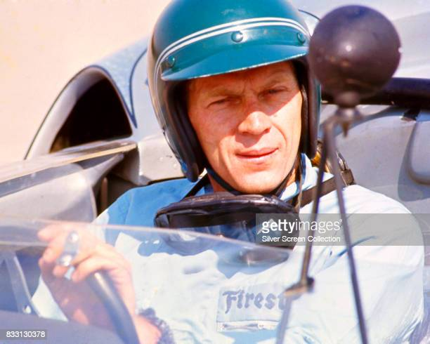 American actor Steve McQueen in Firestone racing driver suit sitting inside a Lola T70 SL70/14 car at Riverside Raceway in Riverside California circa...