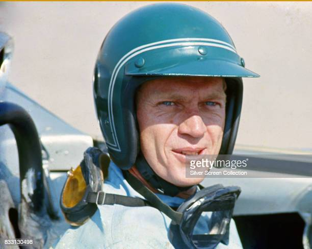 American actor Steve McQueen in Firestone racing driver suit sitting inside a Lola T70 SL70/14 car, at Riverside Raceway in Riverside, California,...