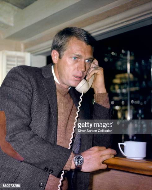 American actor Steve McQueen leans on a counter as he talks on the telephone mid 1960s