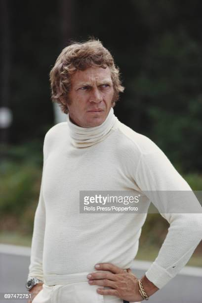 American actor Steve McQueen pictured wearing Nomex fireproof underwear, white trousers and a Rolex Submariner chronograph watch during the making of...
