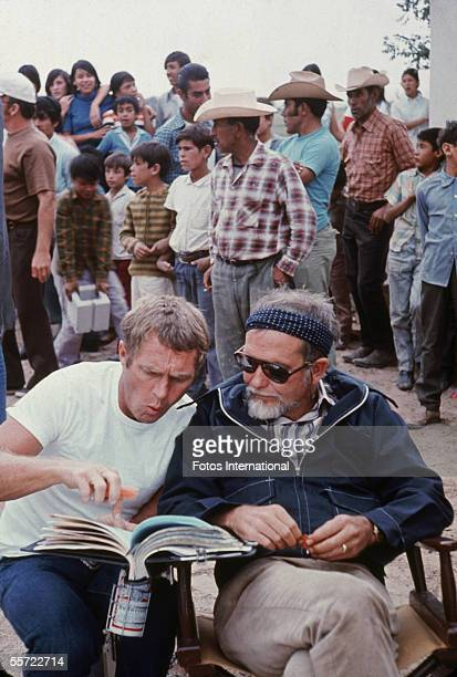 American actor Steve McQueen points to the script as he discusses a scene with director Sam Peckinpah on the set of Peckinpah's 'The Getaway' 1972...