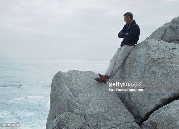 American actor Steve McQueen sitting on rocks by the coast 1965