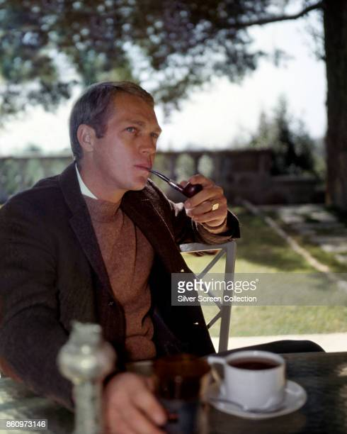 American actor Steve McQueen smokes a pipe as he sits at an outdoor table a cup of coffee in front of him mid 1960s
