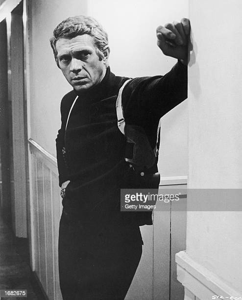 American actor Steve McQueen wearing a gun holster leans in a hallway in a still from the film 'Bullitt' directed by Peter Yates 1968
